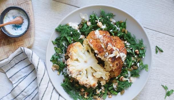 Whole Roasted Cauliflower with Tahini Sauce, Raisins, Hazelnuts and Green Herbs