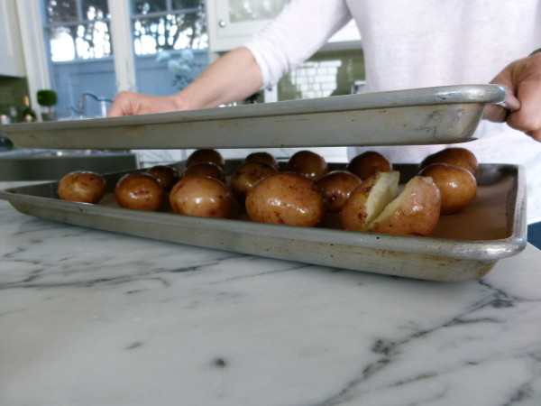 put another baking sheet on top to flatten potatoes