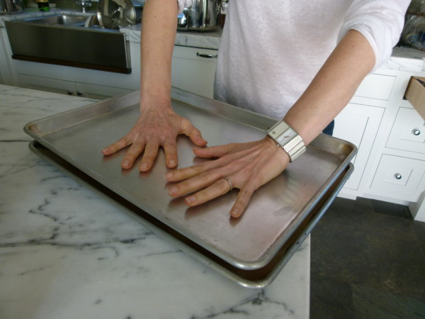 press down on the baking sheet to flatten the potatoes